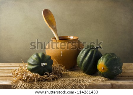 Still life with acorn squash on wooden tabletop against grunge background - stock photo