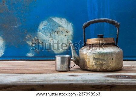 Still life with antique stainless kettle on wooden table over grunge background