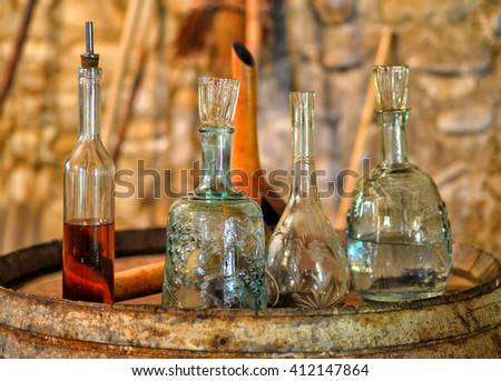 Still life with antique utensils for wine and brandy in the ancient wine cellar on the old oak barrel - stock photo