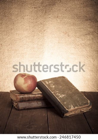 Still life with apple and a stack of old books on old wooden table. Toned