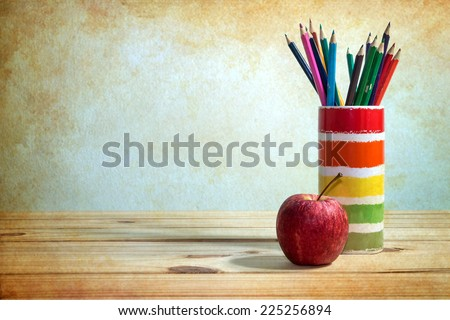 still life with apple and colored pencil on wooden table over grunge background - stock photo