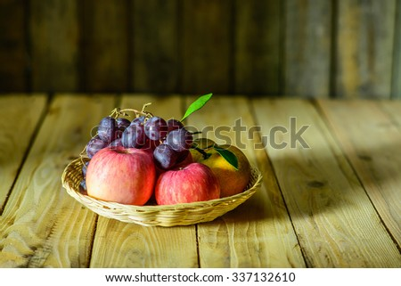 Still life with apples, grape and  orange on wooden board. - stock photo
