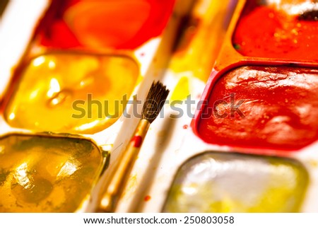 still life with aquarelle and brush, shallow depth of field - stock photo