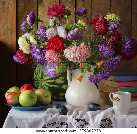 Still life with autumn bouquet of garden flowers in a white jug, apples and watermelon, in the background . - stock photo