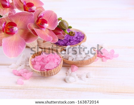Still life with beautiful blooming orchid flower  and wooden spoons with sea salt, on color wooden background