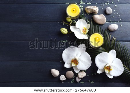 Still life with beautiful blooming orchid flower, candles and pebbles, on wooden background - stock photo