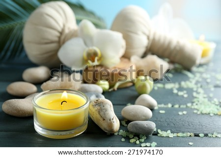 Still life with beautiful blooming orchid flower, spa treatment on wooden table, on bright background - stock photo