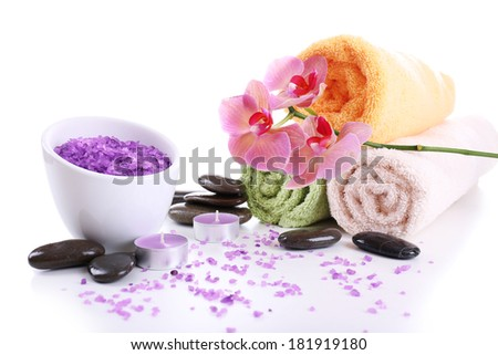 Still life with beautiful blooming orchid flower, towels and bowl with sea salt, isolated on white - stock photo