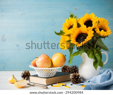 Still life with beautiful sunflowers bouquet in white vase with apples, pine cones and book on blue wooden background. Greeting card concept. - stock photo