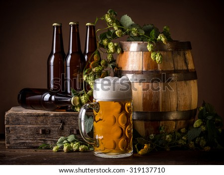 Still life with beer, fresh hops and barrel