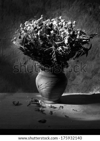 Still life with black and white  bouquet of dried roses in clay vase with grunge background - stock photo