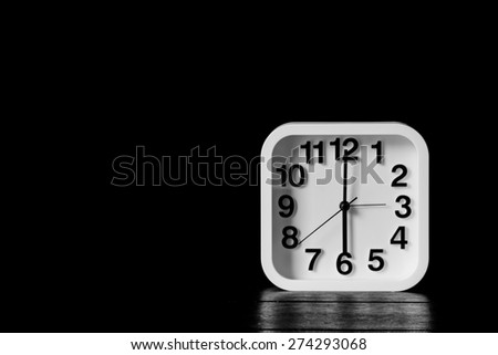 Still life with black and white desktop clock on wood table, low key image - stock photo