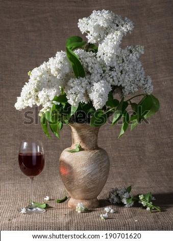 Still life with blooming branches of lilac in vase - stock photo