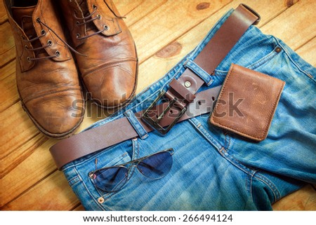 Still life with blue jeans and boots on wooden background - stock photo