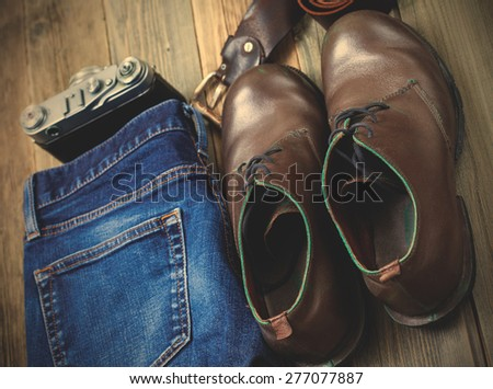 Still life with blue jeans, brown boots, leather belt and rangefinder camera on aged textured boards. instagram image retro style