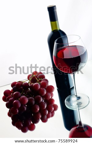 Still-life with bottle and glass of red wine over white background. - stock photo