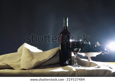 Still life with bottle of red wine near wineglass and grape