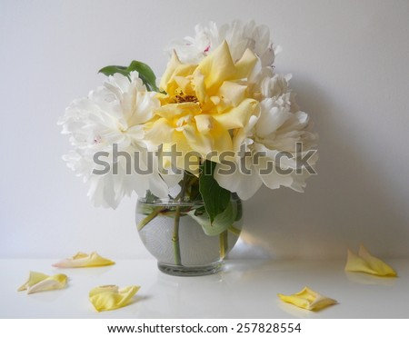 Still life with bouquet of peony flowers and roses in a vase. Floral still life with white peonies and yellow rose and petals. Home decoration with bouquet of flowers. - stock photo