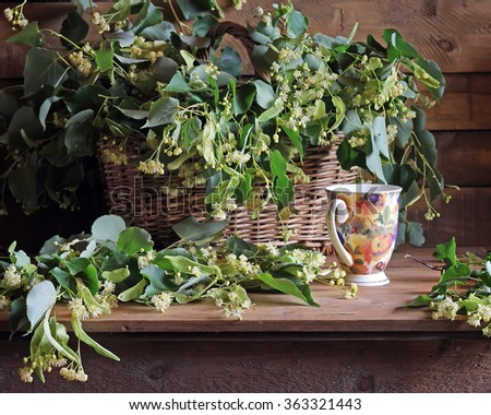 Still life with branches of the blossoming linden and a cup on a wooden table against from boards.