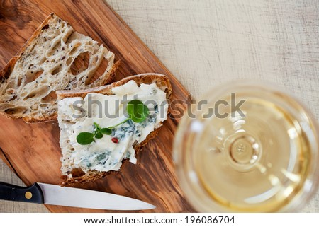 Still life with bread, cheese and glass of wine - stock photo