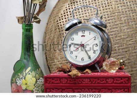Still life with broken alarm clock, old glass vase with dead rose, classic perfume, vintage box. - stock photo