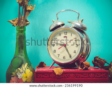 Still life with broken alarm clock, old glass vase with dead rose, vintage box. - stock photo