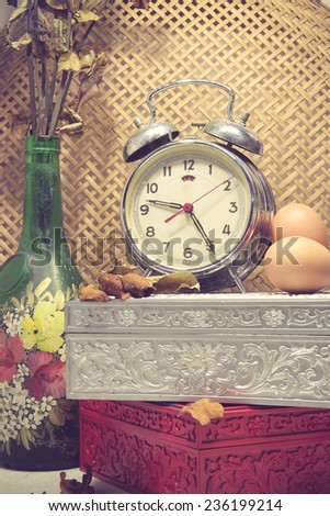 Still life with broken alarm clock, old glass vase with dead rose, vintage box, eggs, toned image. - stock photo