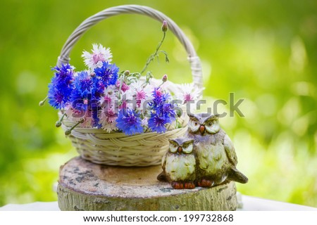 Still life with bunch of beautiful flowers in the basket and owls figurine - stock photo