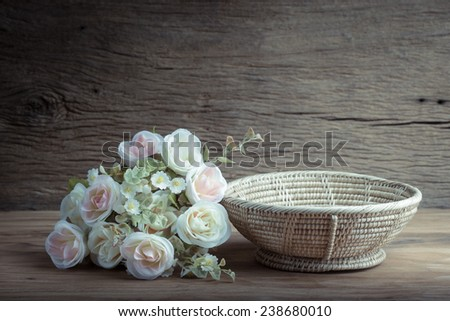 Still life with  bunch of roses and empty basket on wooden table - stock photo