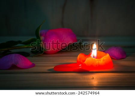 still life with candle and rose flower on wooden table over grunge background, Valentine concept. - stock photo