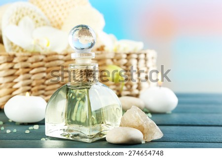 Still life with candle, pebbles and  spa treatment on wooden table, on bright background - stock photo