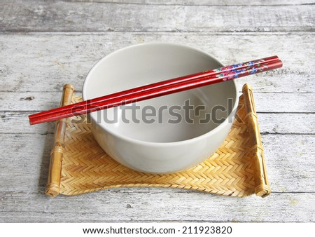 still life with ceramic bowl and chopsticks in bamboo tray on wooden table.  - stock photo