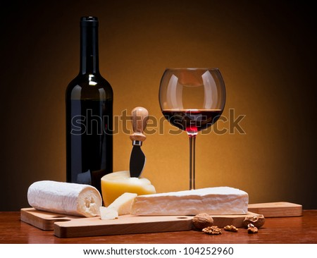 still life with cheese and red wine on a wooden table - stock photo
