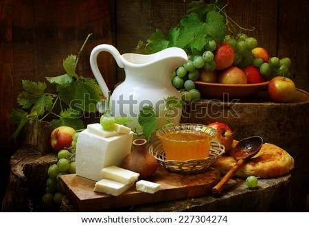 Still-life with cheese both ripe juicy fruit and fragrant honey both salty cheese and a white jug - stock photo