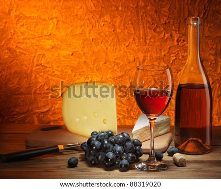 Still-life with cheese, grapes and glass and bottle of red wine.