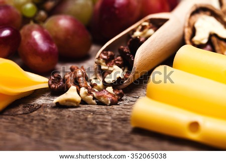 Still life with cheese, grapes, nuts and chili pepper on a wooden table - stock photo