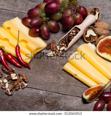 Still life with cheese, grapes, nuts and chili pepper on a wooden table
