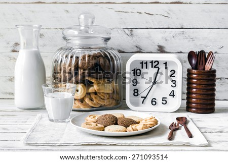 Still life with chocolate chip and butter cookies on white ceramic dish with glass of milk, white clock and wooden spoon on table background - stock photo