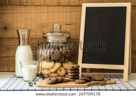 Still life with chocolate chip butter cookies on wood block and in  the canister with bottle of milk and blackboard on wood table - stock photo