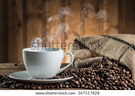 still life with coffee beans and cup on the wooden background  - stock photo
