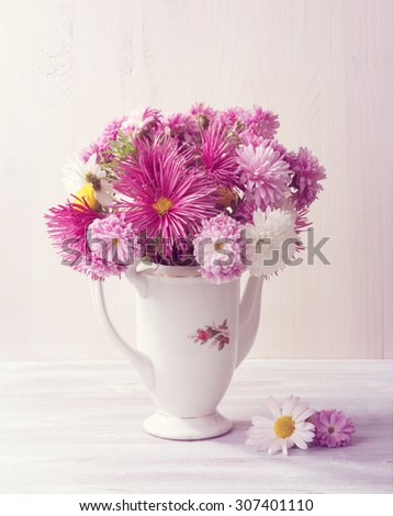 Still life with colourful chrysanthemums bunch on  white wooden board. Toned image - stock photo
