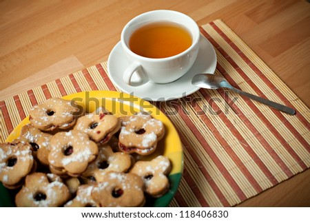 Still life with cookies and tea. Focused on cup of tea - stock photo
