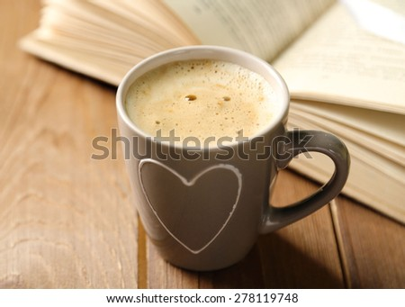 Still life with cup of coffee and book, on wooden table - stock photo