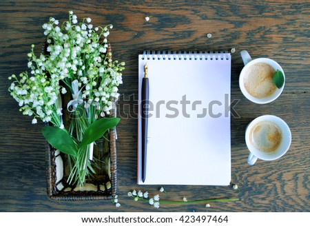 Still life with cup of coffee and flowers a wooden with space for text - stock photo