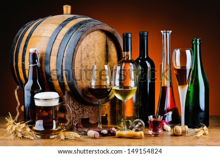 still life with different alcoholic drinks and wooden barrel - stock photo