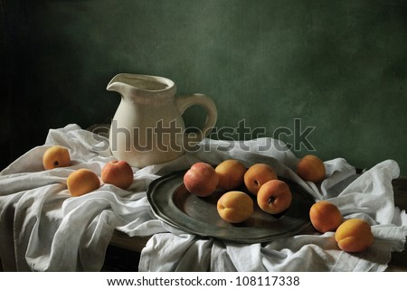 Still life with drapery and apricots - stock photo