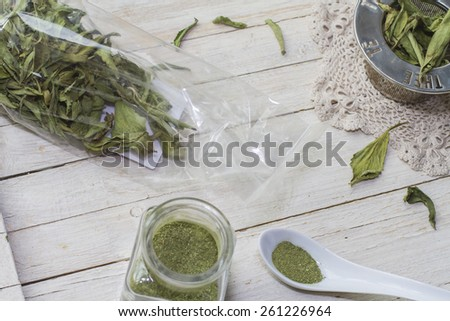 Still life with dried stevia leaves in a plastic bag, glass bottle with stevia powder and sieve for infusion. - stock photo