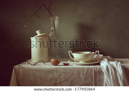 Still life with egg shell, porcelain and a glass bottle - stock photo