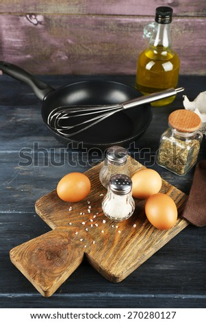 Still life with eggs and pan on wooden background