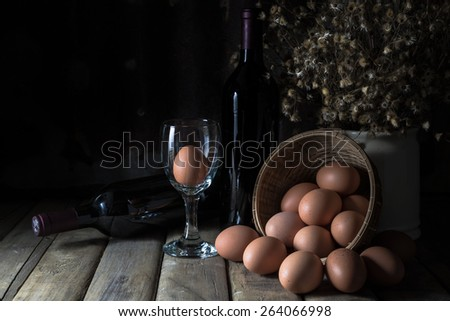 Still life with eggs, wine bottle, dry little flower on wood table and rustic steel plate background - stock photo